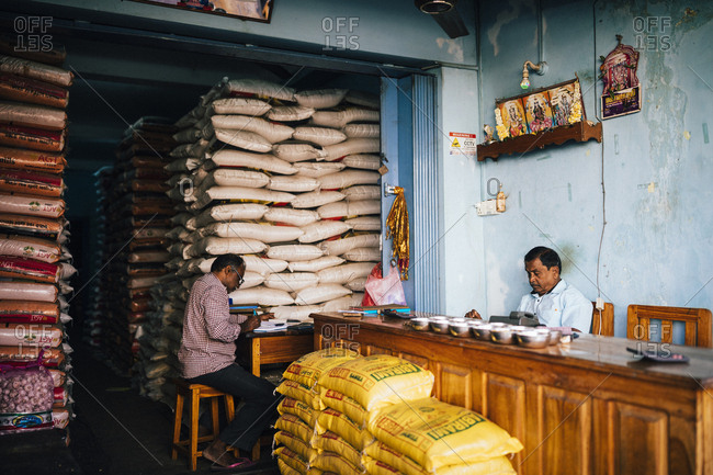 Jaffna, Sri Lanka - February 9, 2018: Men working in a quiet wholesale grain shop at the central market