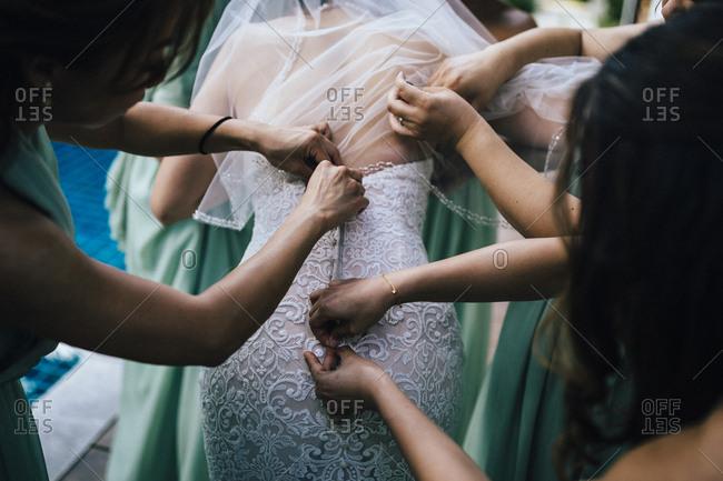 Ko Samui, Thailand - December 11, 2017: Bridesmaids helping bride put on wedding dress