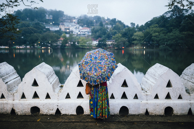 Kandy, Sri Lanka - January 31, 2018: A woman in colorful dress looks out over Bogambara Lake