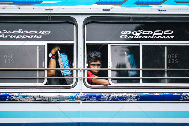 Kandy, Sri Lanka - January 31, 2018: A young man peers out of a bus window