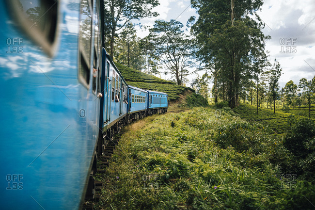 Ella, Sri Lanka - February 1, 2018: A train cuts its way through mountains and tea plantations in hill country