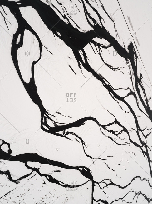 Abstract aerial view of water tributary in snow in icelandic landscape.