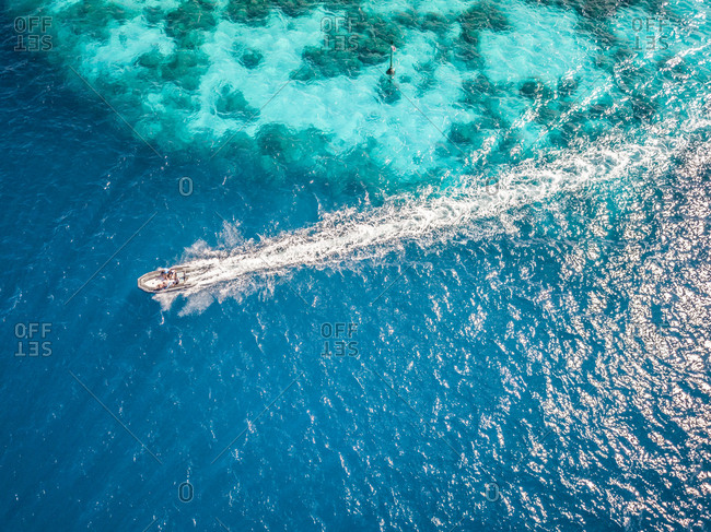 Aerial view of people in a boat in the turquoise sea of Bora-Bora, French Polynesia.