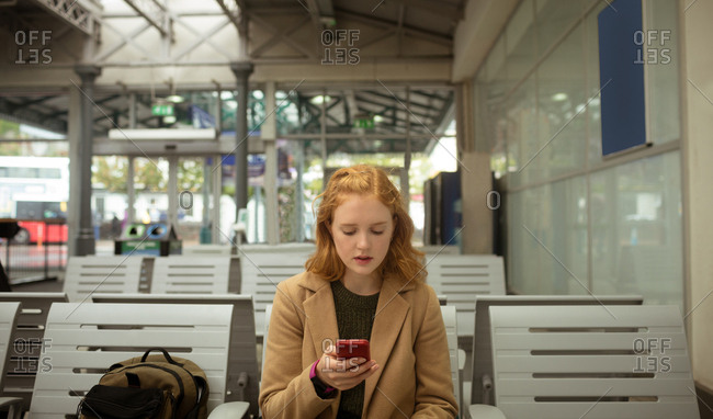 Young woman using her mobile phone at bus stop