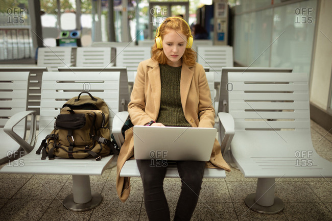 Young woman listing to music while working on laptop