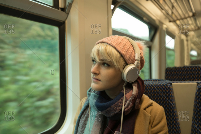 Young woman in warm clothing listing to music on headphones
