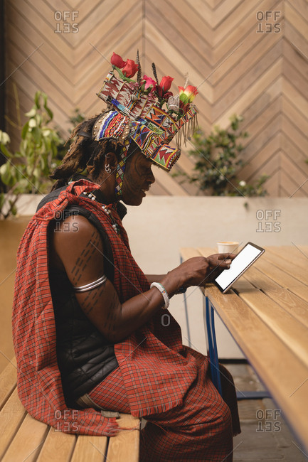 Maasai man in traditional clothing using digital tablet