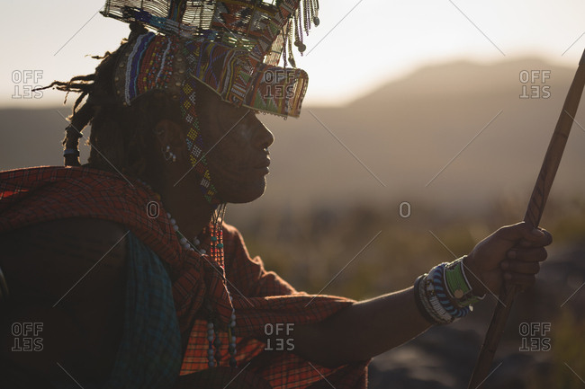 Maasai man in traditional clothing sitting at countryside