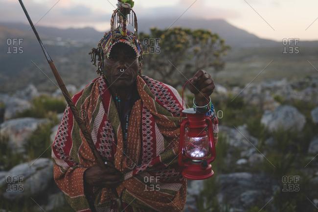 Maasai man holding lantern at countryside