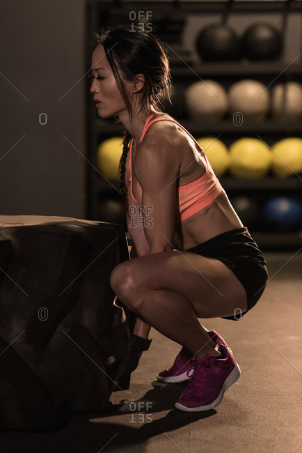 Fit woman exercising with heavy tire