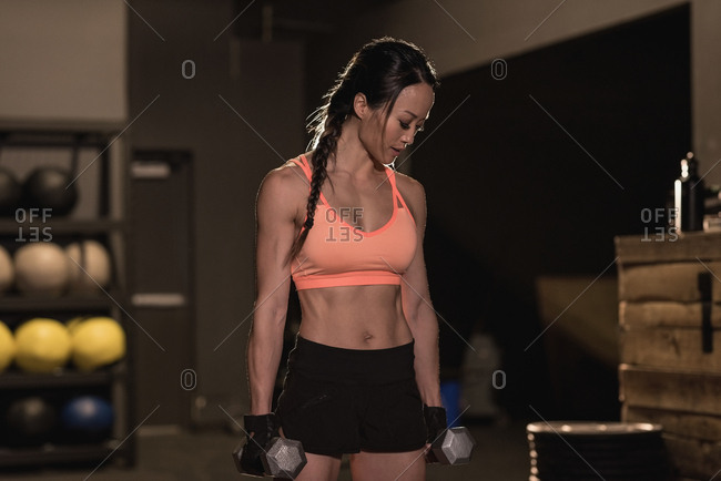 Fit woman exercising with dumbbells