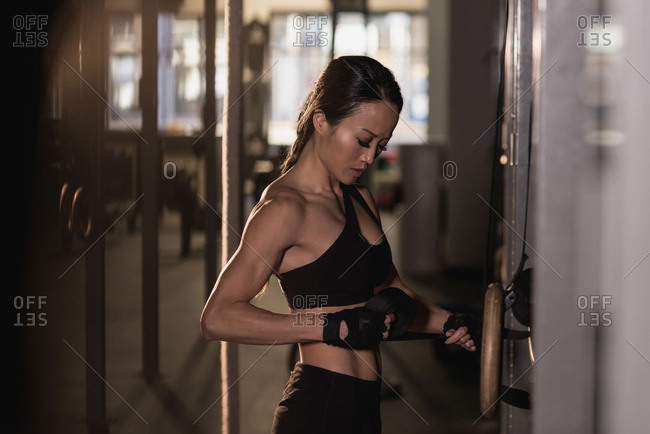 Fit woman adjusting belt while exercising