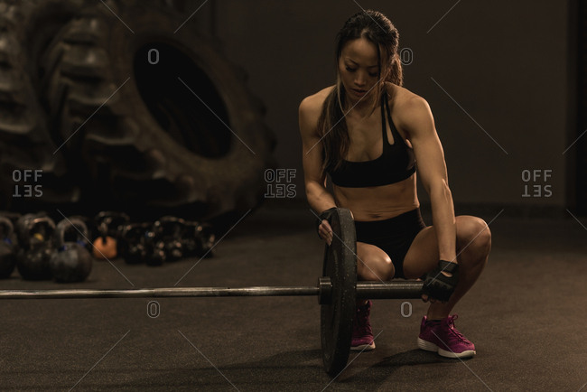 Fit woman adjusting barbell
