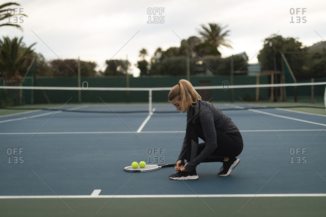 Woman tying her shoelaces in tennis court