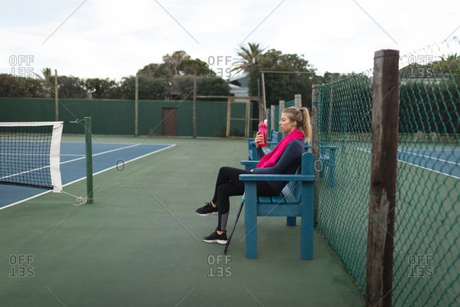 Woman drinking water in tennis court