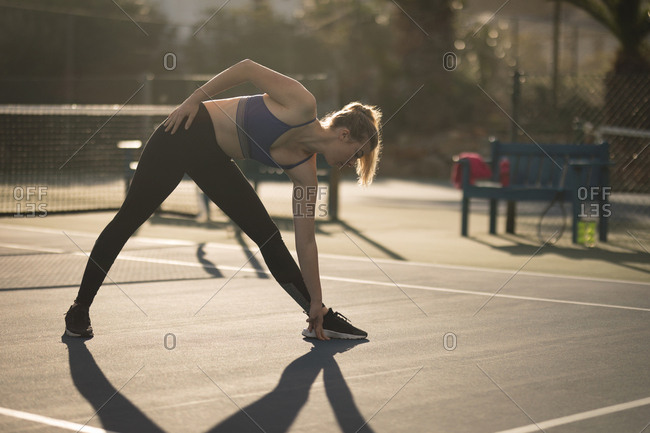 Woman doing stretching exercise in tennis court