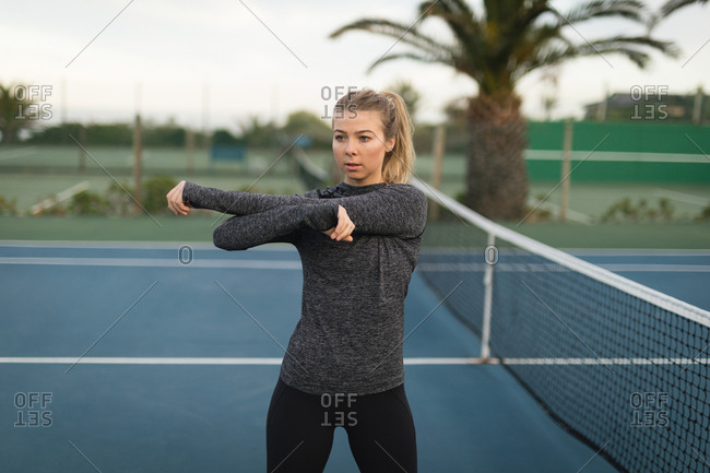 Woman performing stretching exercise in the tennis court