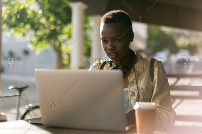 Woman using laptop in outdoor cafe