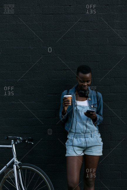 Woman having coffee while using mobile phone