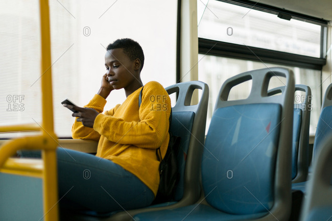 Woman using mobile phone while travelling in bus