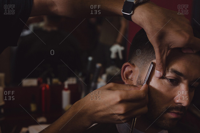 Man getting his hair trimmed with straight razor