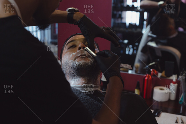 Man getting his beard shaved with straight razor