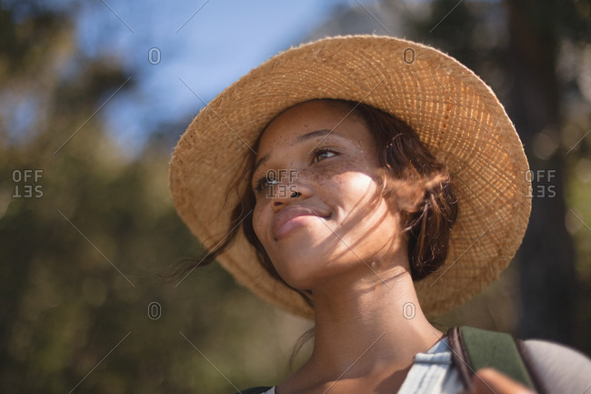 Female hiker in straw hat standing at countryside