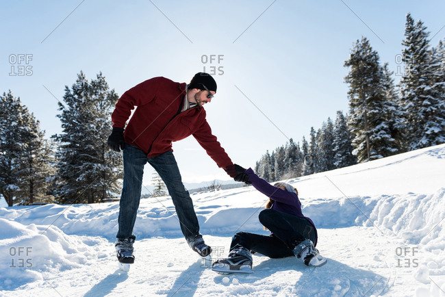 Man helping woman to rise up while skating in snowy landscape