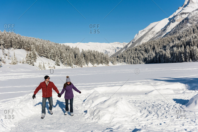 Couple skating together in snowy landscape
