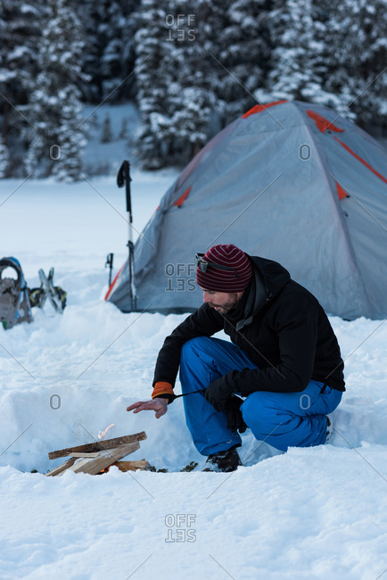 Man preparing bonfire near tent in snowy landscape
