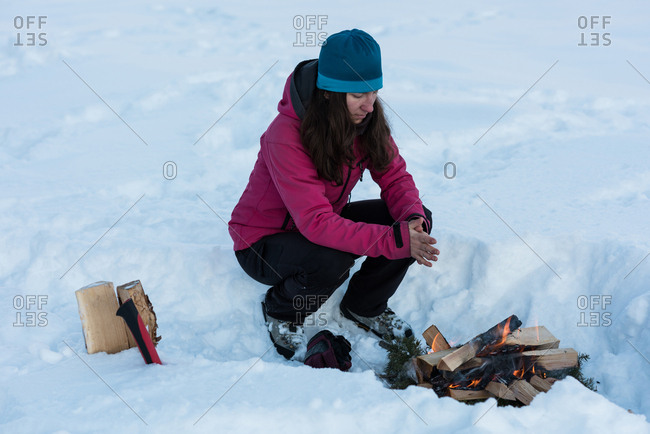 Woman warming up by the bonfire during winter