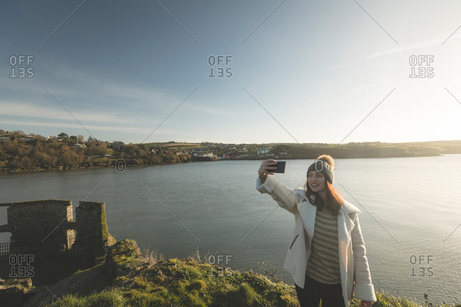 Woman taking selfie with mobile phone near riverside