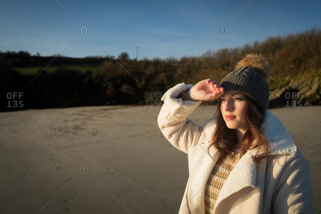 Woman shielding her eyes near riverside