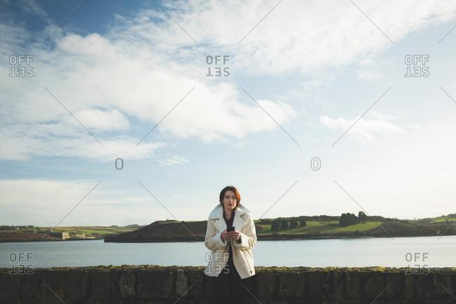 Woman using mobile phone near riverside