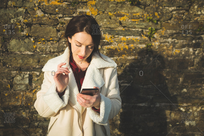 Woman using mobile phone against wall