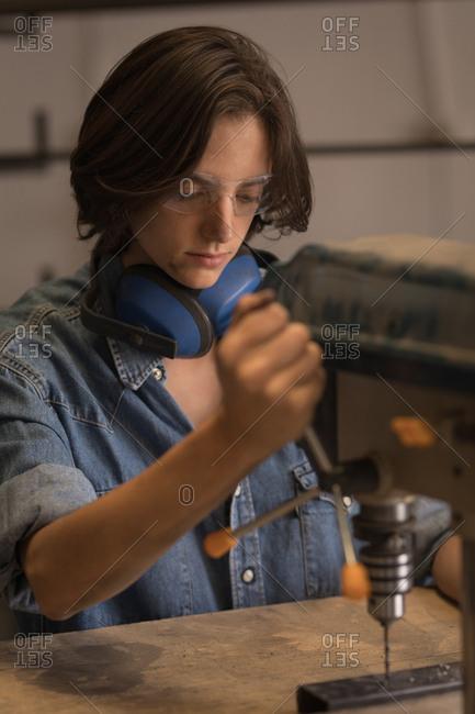 Female welder using vertical drilling machine