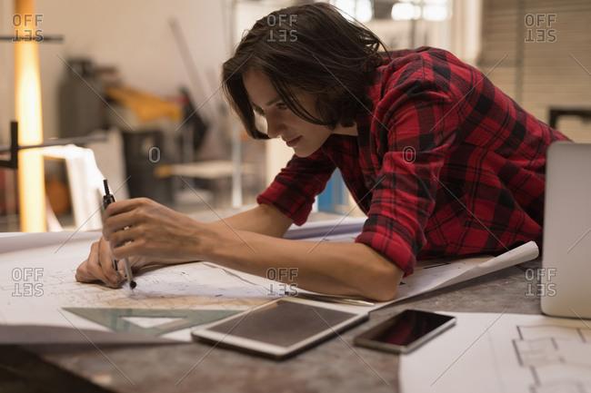 Female welder using compass in workshop