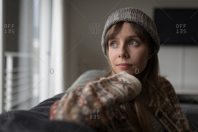 Woman in woolly hat in living room at home