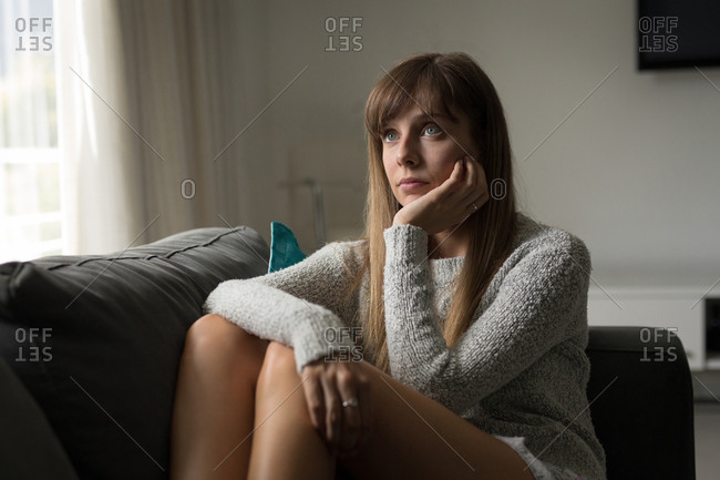 Woman relaxing in living room at home