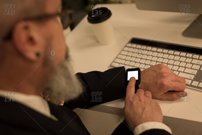 Business executive using smartwatch at desk