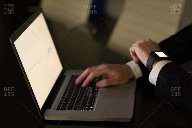 Businessman checking time while using laptop at desk