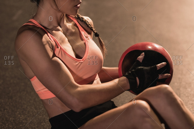 Mid section of fit woman exercising with equipment