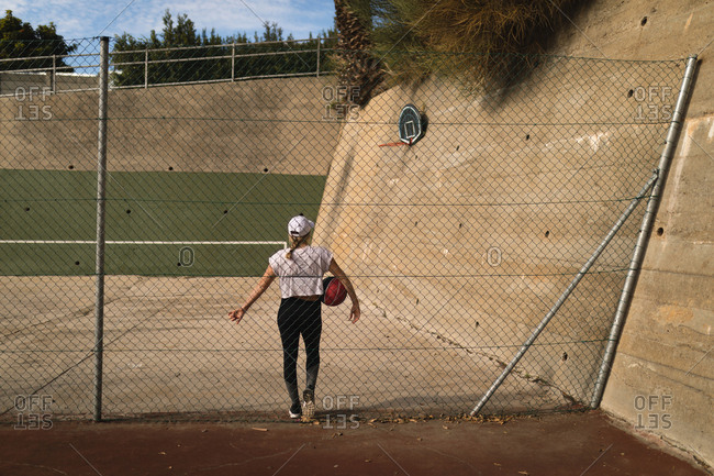 Woman standing with basketball in the basketball court