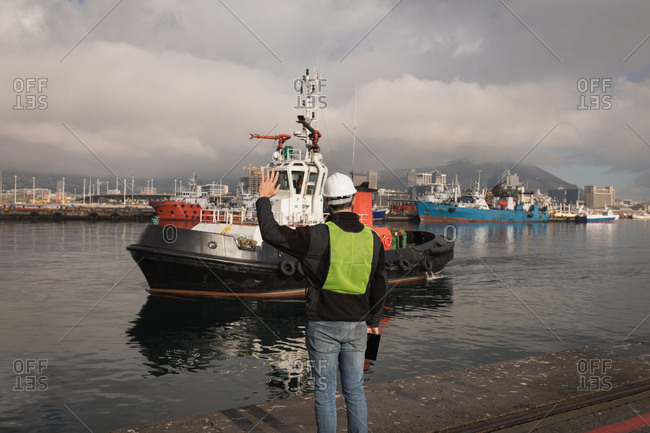 Dock worker waving hand to sailing boat