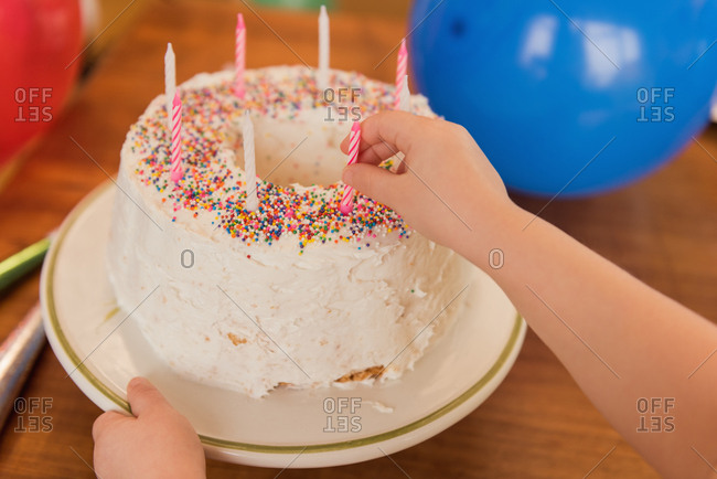 Girl putting candle on birthday cake