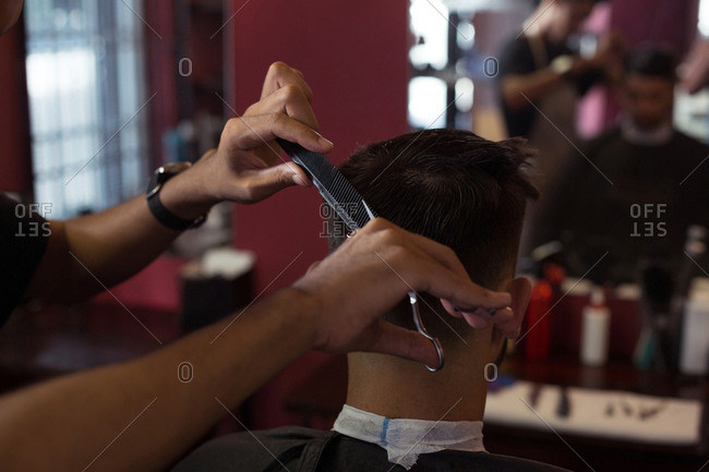 Man getting his hair trimmed with scissor