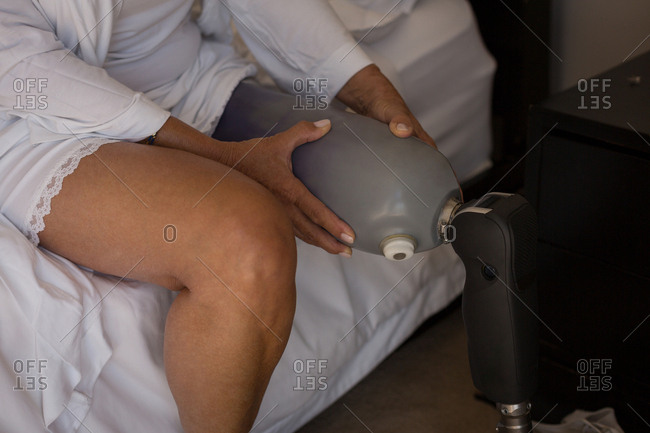 Woman with prosthetic leg in bedroom at home