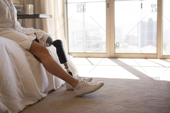 Woman with prosthetic leg in bedroom