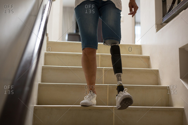 Mature woman with prosthetic leg moving down from stairs