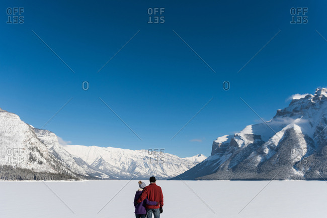 Couple standing with arm around in snowy landscape